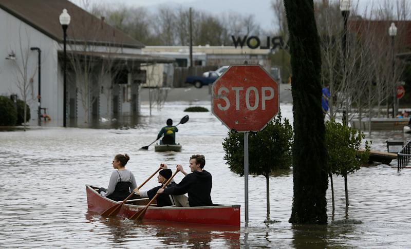 People paddle and row through the flooded Barlow Market District, Feb. 27, 2019, in Sebastopol, Calif. (Photo: Eric Risberg/AP)