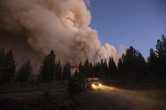 A plume of smoke rises over a roadway as the Sugar Fire, part of the Beckwourth Complex Fire, burns in Plumas National Forest, Calif., on Thursday, July 8, 2021. (AP Photo/Noah Berger)