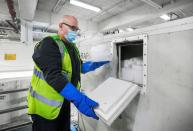 A KLM Cargo worker puts dry ice in a cool box at Amsterdam's Schiphol Airport