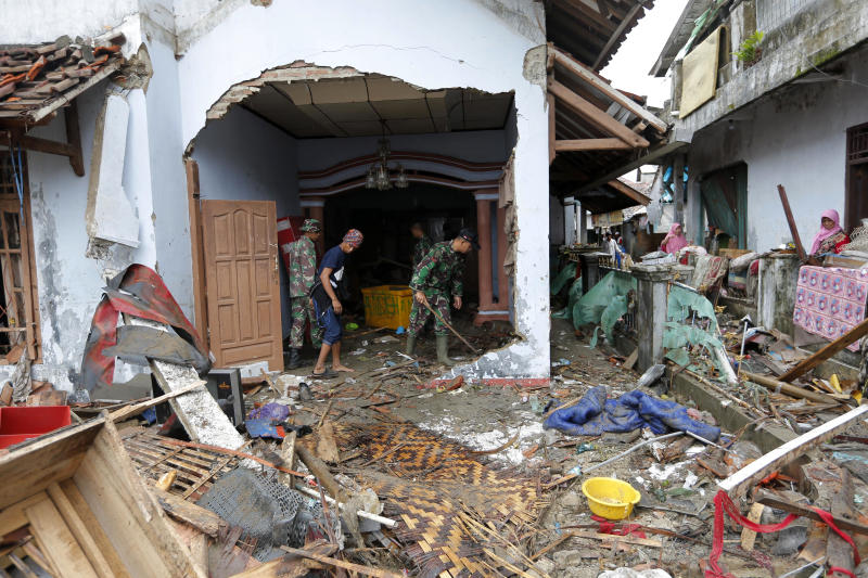 Indonesian soldiers and people clean up the debris following the tsunami in Sumur, Indonesia, Tuesday, Dec. 25, 2018. The Christmas holiday was somber with prayers for tsunami victims in the Indonesian region hit by waves that struck without warning Saturday night.(AP Photo/Tatan Syuflana)