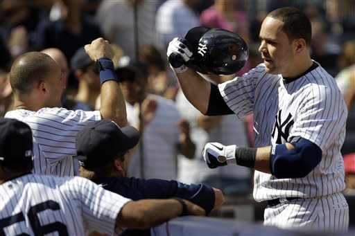 New York Yankees' Derek Jeter, left, greets Russell Martin at the dugout steps after Martin hit a third-inning, three-run home run against the Tampa Bay Rays in their baseball game at Yankee Stadium in New York, Sunday, Sept. 16, 2012. (AP Photo/Kathy Willens)