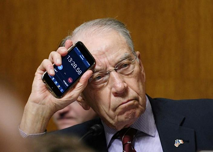 FILE PHOTO: Sen. Chuck Grassley, R-IA, Chairman holds up the timer on his phone while Se. Cory Booker, D-NJ makes an impassioned speech during the Senate Judiciary Committee meeting