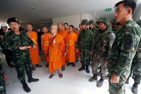 Soldiers and Buddhist monks are seen during an inspection of the Wat Phra Dhammakaya temple, in Pathum Thani province