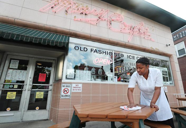 Bobbie Jackson, who has been working at Michael Trecaso's Mary Coyle for 10 years, wipes down a table in the outside patio in Highland Square in Akron on Wednesday June 9, 2021. The restaurant ice cream shop is currently carry out only.