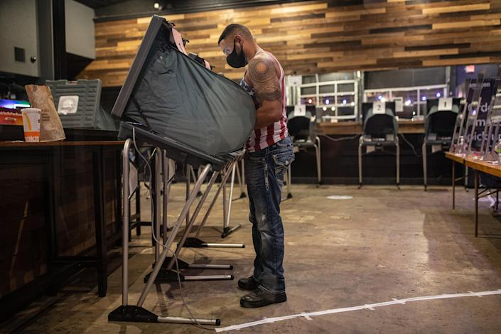 Joseph Williams votes at BUDDY'S bar in Houston on Election Day, Nov. 3, 2020. (Tamir Kalifa/The New York Times)