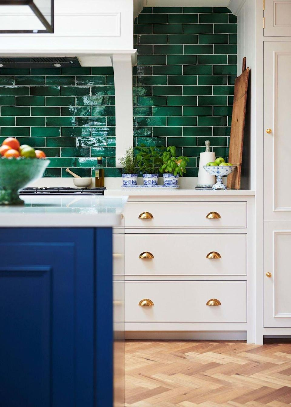 """<p>If you want your white kitchen cabinets to stand out, go for a contrast. Jewel-toned accents, such as emerald green tiling, sapphire blue doors, or amethyst accessories will make your whites appear crisper and brighter. Metallic hardware is the perfect compliment for this design scheme. <br></p><p>Pictured: <a href=""""https://www.neptune.com/kitchen/chichester/"""" rel=""""nofollow noopener"""" target=""""_blank"""" data-ylk=""""slk:Chichester kitchen at Neptune"""" class=""""link rapid-noclick-resp"""">Chichester kitchen at Neptune</a></p>"""