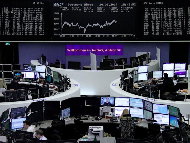 Traders work at their desks in front of the German share price index, DAX board, at the stock exchange in Frankfurt, Germany, March 20, 2017.