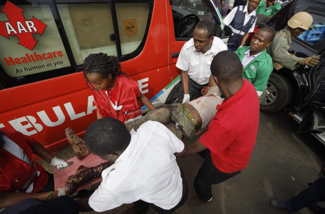 A wounded member of Kenyan special forces with two tourniquets around his legs is carried from a US embassy diplomatic vehicle into an ambulance by paramedics at the scene Wednesday, Jan. 16, 2019 in Nairobi, Kenya. Extremists stormed a luxury hotel in Kenya's capital on Tuesday, setting off thunderous explosions and gunning down people at cafe tables in an attack claimed by Africa's deadliest Islamic militant group. (AP Photo/Ben Curtis)