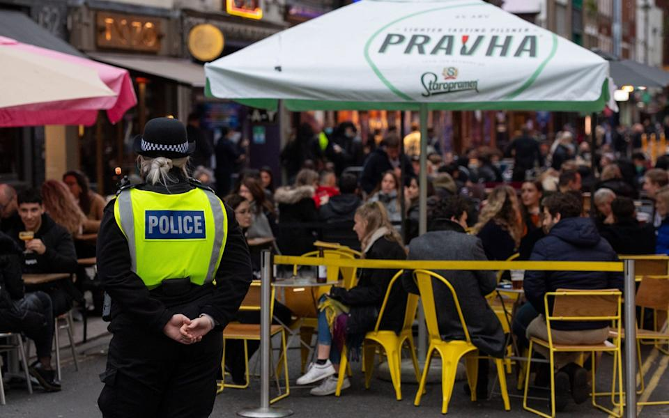 Police monitor people seated outside bars and restaurants in Soho, London, on the first day after the city was put into Tier 2 restrictions to curb the spread of coronavirus.  - Dominic Lipinski/PA Wire