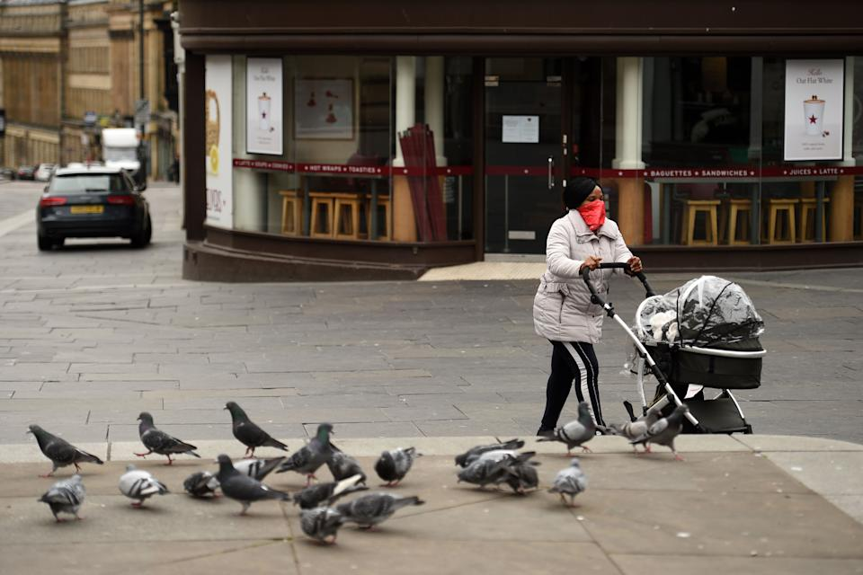 A woman wearing a scarf as a protective face mask, pushes a pram through the centre of Newcastle upon Tyne, Thursday lunchtime in north-east England on April 9, 2020 as Britain continued to battle the outbreak of new coronavirus and the governement prepared to extend the nationwide lockdown. - The disease has struck at the heart of the British government, infected more than 60,000 people nationwide and killed over 7,000, with another record daily death toll of 938 reported on April 8. A testing centre opened in Gateshead on April 9, 2020 as the government ramped up its testing of NHS staff for the new coronavirus. (Photo by Oli SCARFF / AFP) (Photo by OLI SCARFF/AFP via Getty Images)