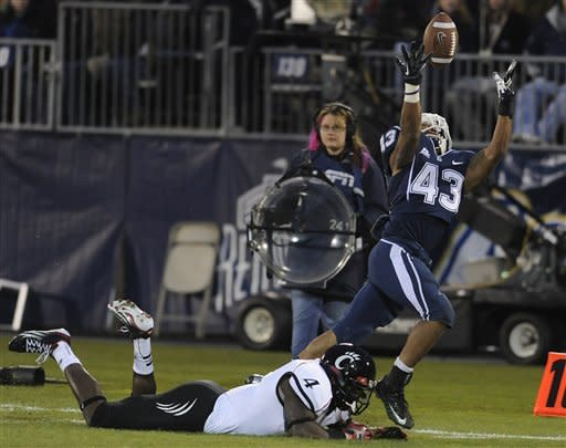 Connecticut running back Lyle McCombs (43) reaches for a pass while defended by Cincinnati linebacker Maalik Bomar (4) during the first half of an NCAA college football game at Rentschler Field in East Hartford, Conn., Saturday, Dec. 1, 2012. The pass was incomplete. (AP Photo/Jessica Hill)