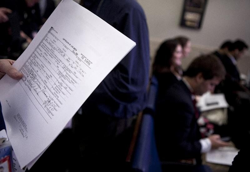 A reporter holds a copy of President Barack Obama's long form birth certificate in 2011 (AFP Photo/BRENDAN SMIALOWSKI)