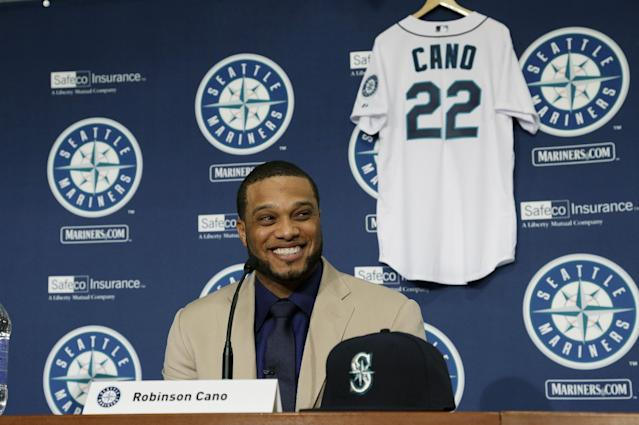 With his new jersey waiting behind him, Robinson Cano smiles as he is introduced as the newest member of the Seattle Mariners baseball team on Thursday, Dec. 12, 2013, in Seattle. (AP Photo/Ted S. Warren)