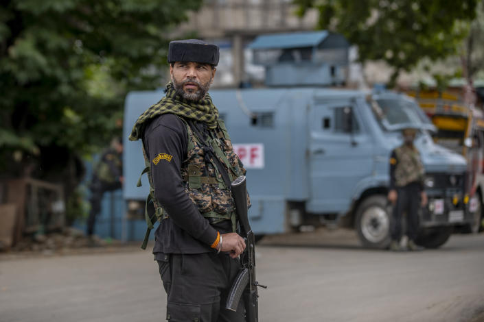 An Indian paramilitary soldier stands guard on a road leading towards the site of a gunfight in Pulwama, south of Srinagar, Indian controlled Kashmir, Wednesday, July 14, 2021. Three suspected rebels were killed in a gunfight in Indian-controlled Kashmir on Wednesday, officials said, as violence in the disputed region increased in recent weeks. Two residential houses were also destroyed. (AP Photo/ Dar Yasin)