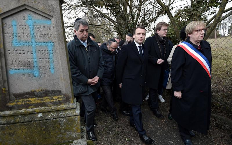 President Emmanuel Macron of France has promised to punish vandals who daubed dozens of graves with swastikas in a Jewish cemetery - REUTERS