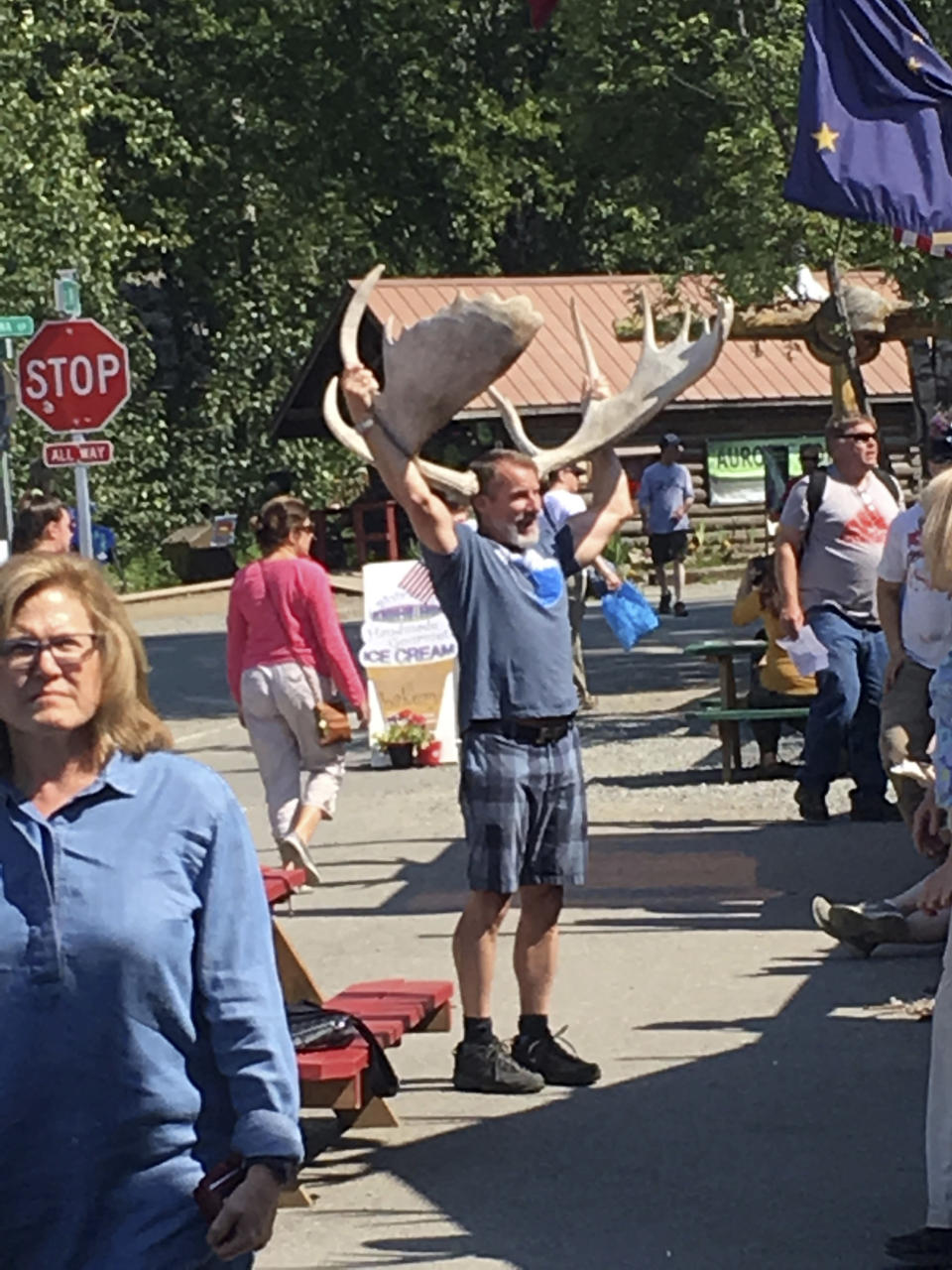 In this July 7, 2018, photo people browse a crowded Main Street in the tourist town of downtown Talkeetna, Alaska. This summer, streets are pretty quiet in Talkeetna after most major cruise ship companies canceled their summer tourist seasons due to the coronavirus pandemic. As a result nearly half of Alaska's annual 2.2 million visitors won't be visiting the nation's northernmost state. (AP Photo/Mark Thiessen)