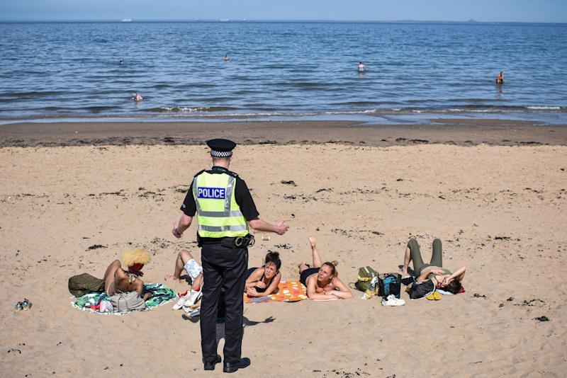A police officer speaks with a group sunbathing in Edinburgh. Source: Getty