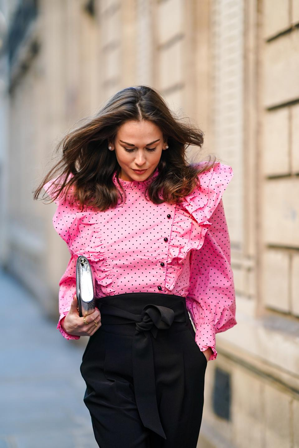 PARIS, FRANCE - NOVEMBER 28: Therese Hellström wears a full Custommade look made of a neon pink ruffled oversized top with puff sleeves and printed polka dots, black pants, a silver shiny crocodile pattern Jimmy Choo bag, on November 28, 2020 in Paris, France. (Photo by Edward Berthelot/Getty Images)