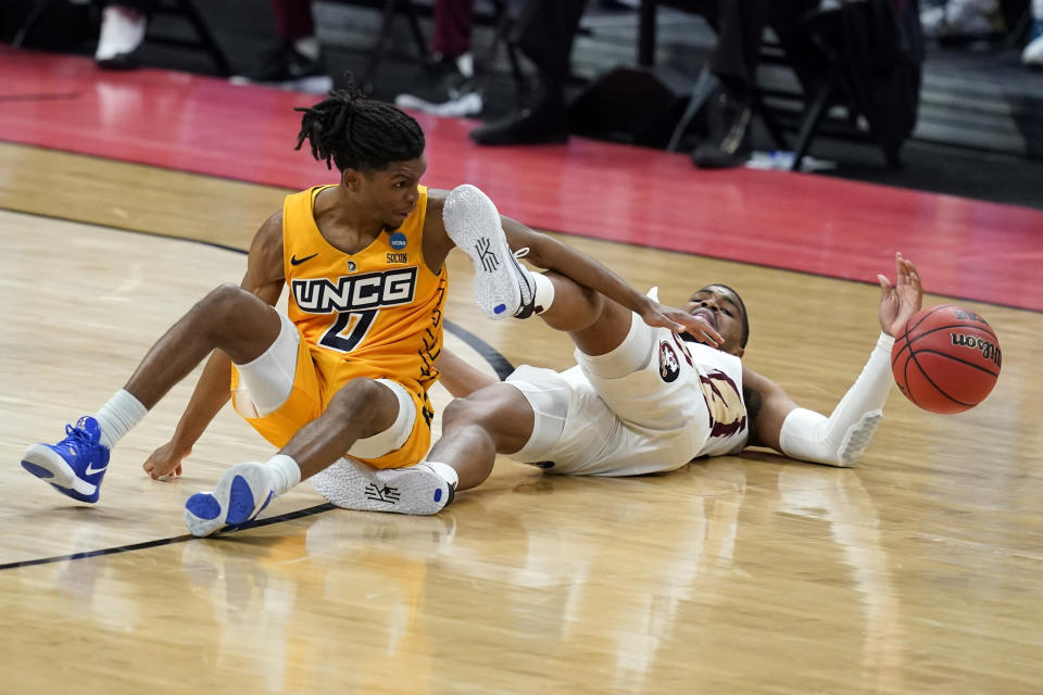 CORRECTS ID TO KEYSHAUN LANGLEY (0), NOT ISAIAH MILLER (1) - UNC-Greensboro's Keyshaun Langley (0) and Florida State's M.J. Walker (23) battle for a loose ball during the second half of a first-round game in the NCAA men's college basketball tournament at Banker's Life Fieldhouse, Saturday, March 20, 2021, in Indianapolis. (AP Photo/Darron Cummings)