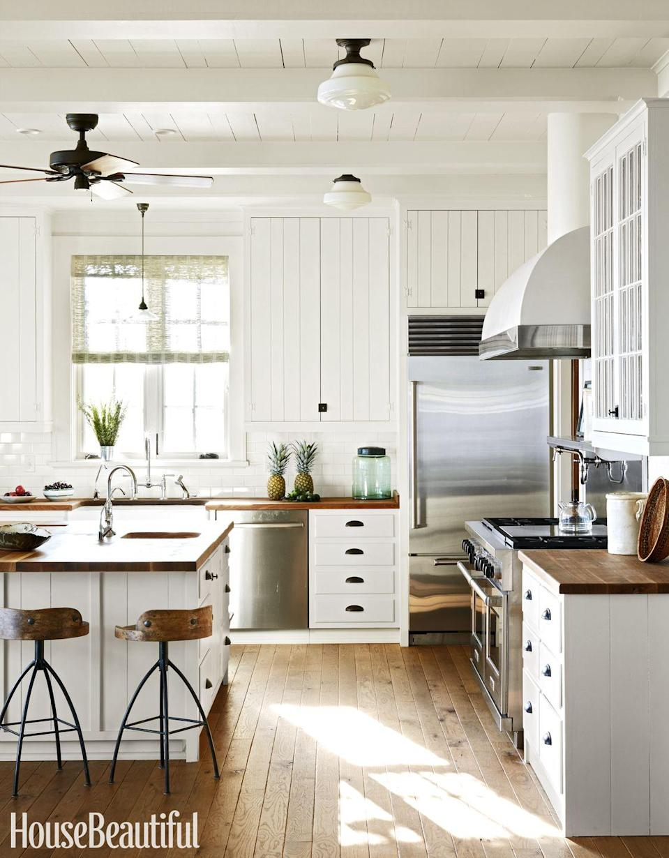 "<p>Pale oak floors have a scrubbed look, and plank cabinetry with painted hinges and black latches give a<span class=""redactor-unlink""> kitchen</span> old-time charm. To top the counters and island, choose a butcher block for warmth and informality, like designer Tammy Connor did here.</p>"