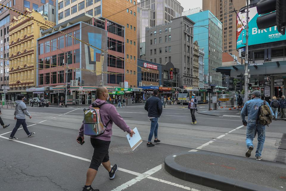 MELBOURNE, AUSTRALIA - NOVEMBER 06: A general view of pedestrians crossing the road at the corner of Flinders and Elizabeth Street on November 06, 2020 in Melbourne, Australia. Lockdown restrictions in Melbourne were lifted on 28 October, with people now able to leave their homes for any reason. Cafes, restaurants, pubs and bars can reopen subject to patron limits while beauty services, tattoo parlours and any other service where you can wear a mask will be able to resume. Up to 10 people from any number of households will be able to gather outdoors, however, Victorians are still required to wear a face mask in public.  (Photo by Asanka Ratnayake/Getty Images)