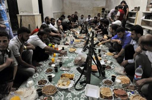 "Syrian rebels break their fast with the ""iftar"" meal during the Muslim fasting month of Ramadan in the northern city of Aleppo on July 24, 2012. A commercial hub and home to 2.5 million people, Syria's second city Aleppo has become a new front in the country's 16-month uprising, after being largely excluded from the violence. AFP PHOTO / BULENT KILIC"