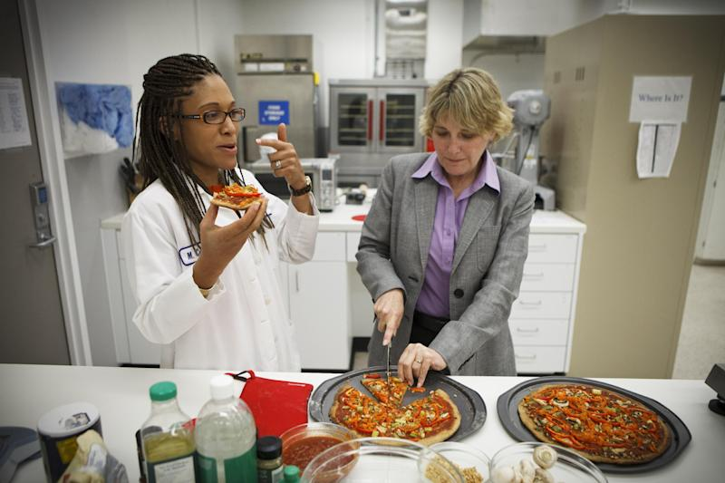 NASA's Advanced Food Technology Project manager Michele Perchonok, right, and Lockeed Martin Sr. Research Scientist Maya Cooper, try a pizza recipe being tested in a kitchen at Johnson Space Center Tuesday, July 3, 2012 in Houston, Texas. NASA is currently planning a mission to Mars, which has gravity, so more options for food preparation, like chopping vegetables, are available as opposed to the dehydrated fare of current space missions. (AP Photo/Michael Stravato)