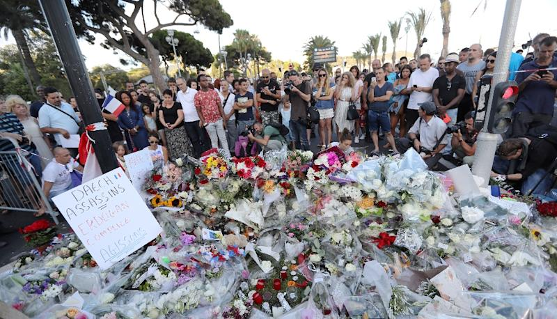 Mourners gather around a makeshift memorial to pay tribute to the victims of a terror attack in the French Riviera city of Nice, on July 15, 2016 (AFP Photo/Valery Hache)
