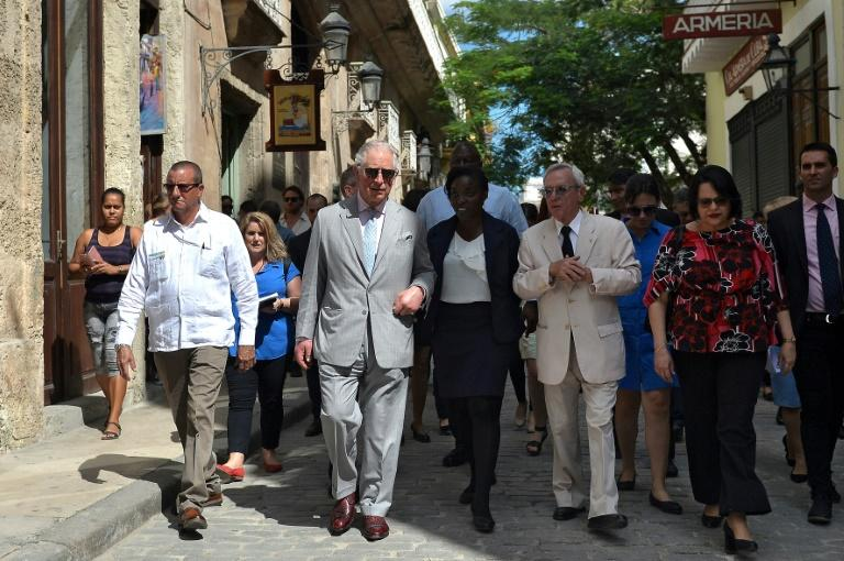 Surrounded by a curious throng of Cubans and foreign tourists, Prince Charles and his wife Camilla were given a guided tour of Havana landmarks by Cuban historian Eusebio Leal(3-R)