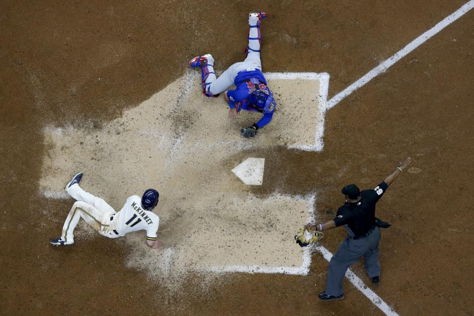 Milwaukee Brewers' Billy McKinney slides safely past Chicago Cubs catcher Austin Romine during the sixth inning of a baseball game Wednesday, April 14, 2021, in Milwaukee. McKinney scored from second on a hit by Corbin Burnes. (AP Photo/Morry Gash)
