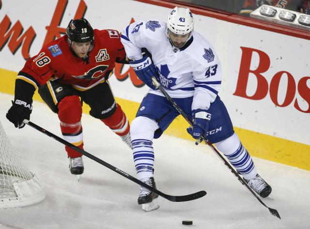 Toronto Maple Leafs' Nazem Kadri, right, chases the puck with Calgary Flames' Matt Stajan during the second period of an NHL hockey game in Calgary, Alberta, Wednesday, Oct. 30, 2013. (AP Photo/The Canadian Press, Jeff McIntosh)
