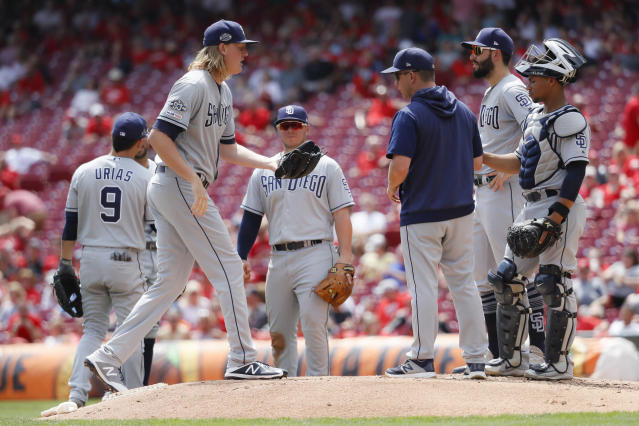San Diego Padres relief pitcher Trey Wingenter, left, takes the mound after relieving pitcher Eric Yardley in the third inning of a baseball game against the Cincinnati Reds, Wednesday, Aug. 21, 2019, in Cincinnati. (AP Photo/John Minchillo)