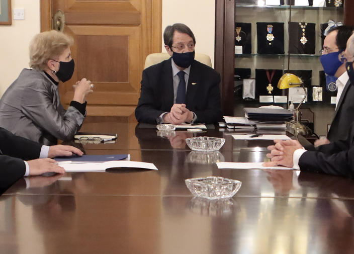In this photo released from Cyprus' Press and Informations Office, Cyprus President Nicos Anastasiades, center, United Nations Secretary General advisor Jane Holl Lute, left, and Cyprus' foreign minister Nicos Christodoulides, right, talk during their meeting at the presidential palace in divided capital Nicosia, Cyprus, on Tuesday, Dec. 1, 2020. Lute is meeting both leaders separately in order to prepare the ground for reunification talks. (Stavros Ioannides, Cyprus' Press and Informations Office via AP)