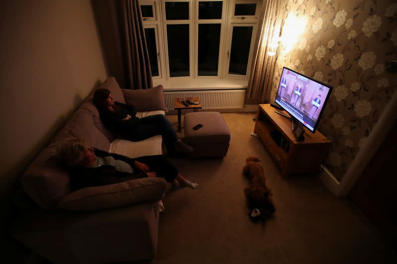 Women watch Britain's Prime Minister Boris Johnson address the nation from a TV screen at a home in Davenham