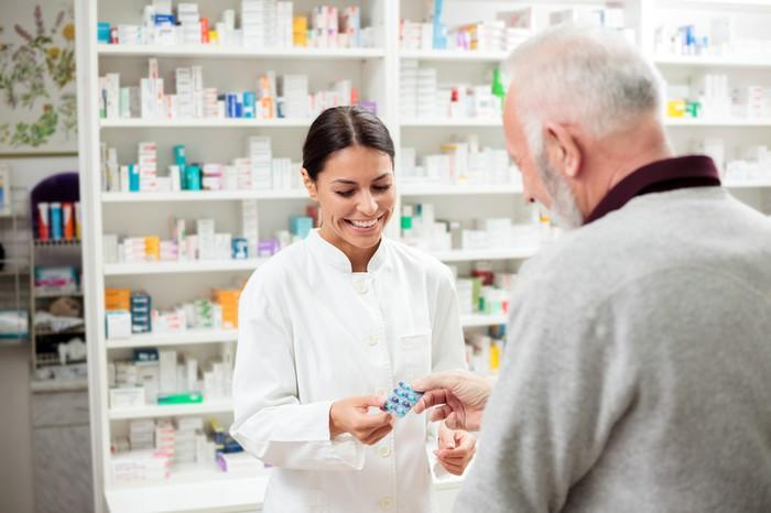 A female pharmacist dispensing medicine to an older man.