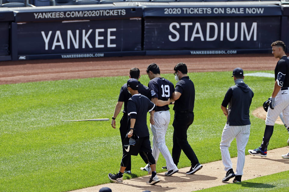 New York Yankees pitcher Masahiro Tanaka (19) is helped off the field by team medical personnel after being hit by a ball off the bat of Yankees Giancarlo Stanton during a baseball a workout at Yankee Stadium in New York, Saturday, July 4, 2020. (AP Photo/Adam Hunger)