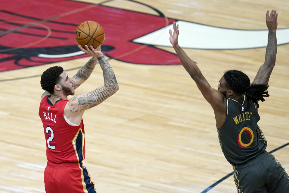 New Orleans Pelicans' Lonzo Ball (2) shoots as Chicago Bulls' Coby White defends during the second half of an NBA basketball game Wednesday, Feb. 10, 2021, in Chicago. (AP Photo/Charles Rex Arbogast)
