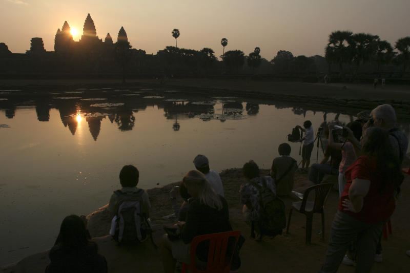 In this March 30, 2008 photo, tourists watch the sunrise at the famed Angkor Wat temple in Siem Reap province, Cambodia. Cambodia has joined hands with Australia in an effort to use the Internet to help preserve its fabled Angkor Wat temple complex. The Australian Embassy announced Thursday, July 4, 2013, that a recently-opened website, angkorsunsets.com, will allow tourists to generate recommendations for where in the 160-square-mile (400-square-kilometer) complex one can watch spectacular sunsets. (AP Photo/Heng Sinith)