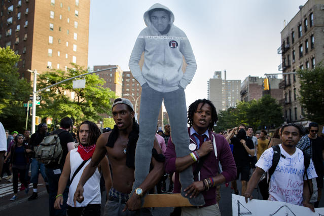 Demonstrators march through the Lower East Side neighborhood of Manhattan in New York, Sunday, July 14, 2013, holding a cut-out of Trayvon Martin during a protest against the acquittal of neighborhood watch member George Zimmerman in the killing of the 17-year-old in Florida. Demonstrators upset with the verdict protested mostly peacefully in Florida, Milwaukee, Washington, Atlanta and other cities overnight and into the early morning. (AP Photo/John Minchillo)