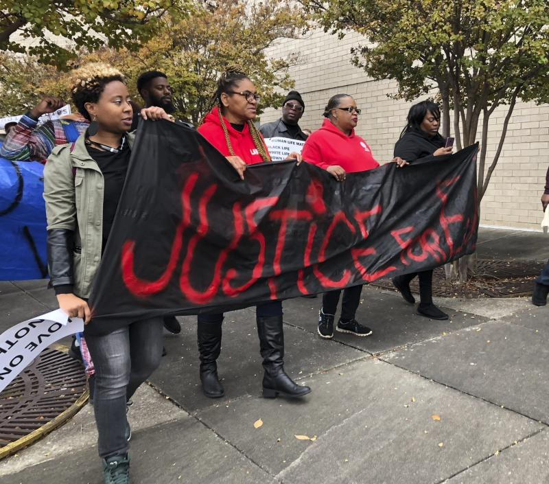 "Protestors carry a sign reading ""Justice for E.J."" during a protest at the Riverchase Galleria in Hoover, Alabama, on Saturday after 21-year-old Emantic Fitzgerald Bradford was fatally shot by police. (ASSOCIATED PRESS)"
