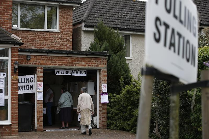 Members of the public vote at a polling station set up in the garage of a house in Croydon on May 7, 2015, as Britain holds a general election (AFP Photo/Adrian Dennis)