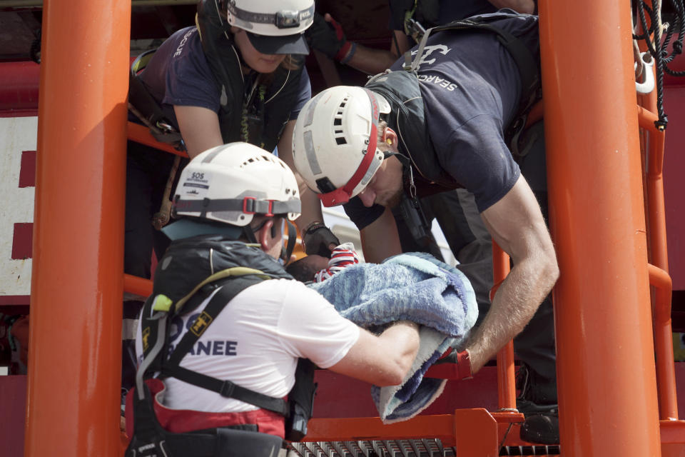 A newborn baby is carried onto the Ocean Viking humanitarian rescue ship after a rescue operation some 53 nautical miles (98 kilometers) from the coast of Libya in the Mediterranean Sea, Tuesday, Sept. 17, 2019. The humanitarian rescue ship Ocean Viking pulled 48 people from a small and overcrowded wooden boat including a newborn and a pregnant woman. (AP Photo/Renata Brito)