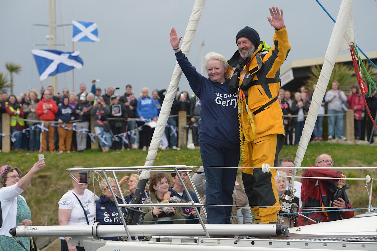 TROON, SCOTLAND - MAY 08:  Gerry Hughes is greeted by his wife Kathleen after sailing his yacht Quest III back into Troon Marina on May 8, 2013 in Troon,Scotland. The 55 year old sailor from Glasgow is the first deaf person to sail single handed around the world, he was greeted back in Scotland by a crowd of  around 300 people.  (Photo by Jeff J Mitchell/Getty Images)