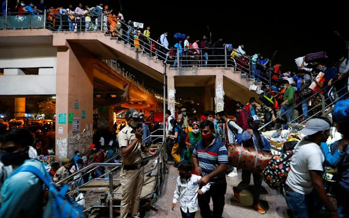 Migrant workers arrive at a bus station to board buses to return to their villages after Delhi government ordered a six-day lockdown to limit the spread of coronavirus in Ghaziabad on the outskirts of New Delhi, India - Adnan Abidi
