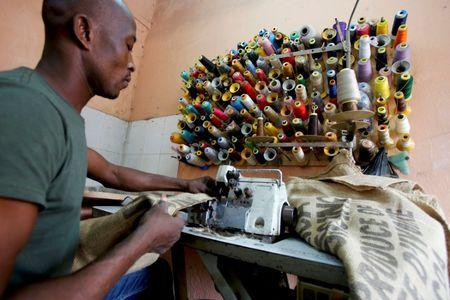 A man works on a sewing machine inside the workshop of Ivory coast fashion designer Liliane Estievenart, 45, in Abidjan, Ivory Coast July 22, 2017. Picture taken July 22, 2017. REUTERS/Thierry Gouegnon