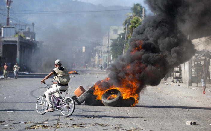 A man rides a bicycle past burning tires set by protesters demanding to know how Petro Caribe funds have been used by the current and past administrations, in Port-au-Prince, Haiti, Wednesday, Oct. 17, 2018. Much of the financial support to help Haiti rebuild after the 2010 earthquake comes from Venezuela's Petro Caribe fund, a 2005 pact that gives suppliers below-market financing for oil and is under the control of the central government. (AP Photo/Dieu Nalio Chery)