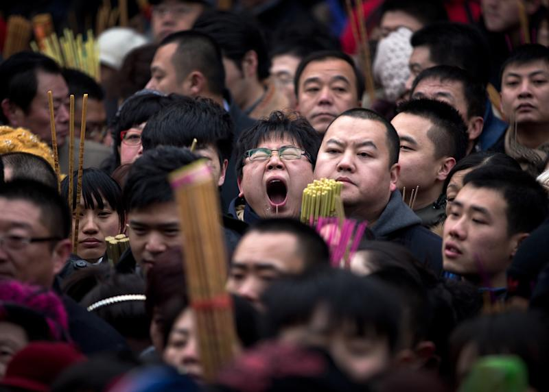A Chinese man, center, yawns as he and other worshippers gather to pray on the first day of Chinese Lunar New Year at Yonghegong Lama Temple in Beijing Sunday, Feb. 10, 2013. Millions across China are celebrating the arrival of the Lunar New Year, the Year of the Snake, marked with a week-long Spring Festival holiday. (AP Photo/Andy Wong)