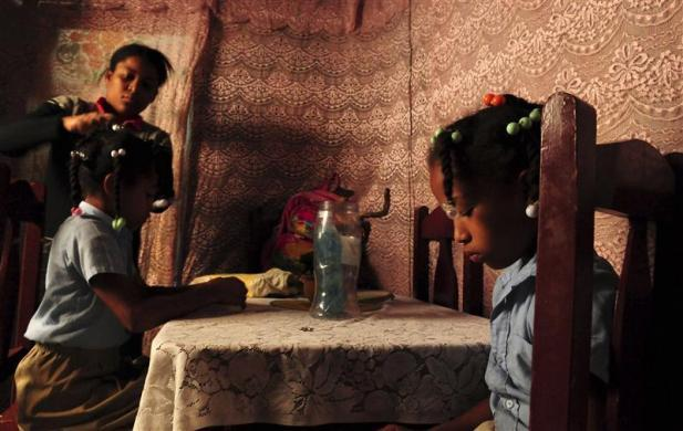 Single mother Evelyn de los Santos combs the hair of her daughters to prepare them for school in Capotillo, at a slum of some 100,000 inhabitants along Ozama River in Santo Domingo, March 7, 2012.