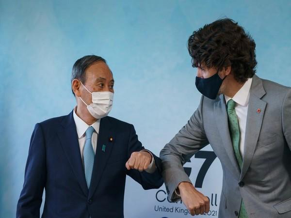 Japanese Prime Minister Yoshihide Suga (l) and his Canadian counterpart Justin Trudeau