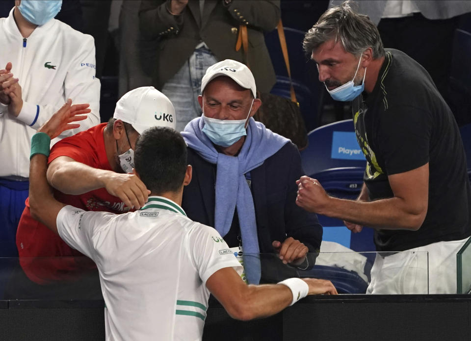 Serbia's Novak Djokovic celebrates with his support team after defeating Russia's Daniil Medvedev during the men's singles final at the Australian Open tennis championship in Melbourne, Australia, Sunday, Feb. 21, 2021.(AP Photo/Mark Dadswell)